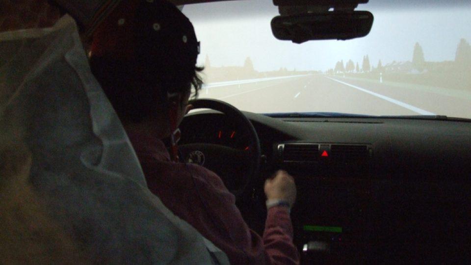 Experiment začal. Řidička má za úkol jet po dálnici dvě hodiny rychlostí 130 km/h. Občas stisknutím tlačítka odpoví na zvukový podnět, vyslaný z velínu