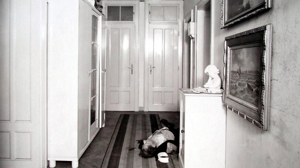 Tělo zavražděného soudního rady vynesené z koupelny do předsíně jeho bytu
