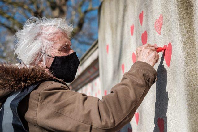 Senior s rouškou malující srdce | foto: Fotobanka Unsplash