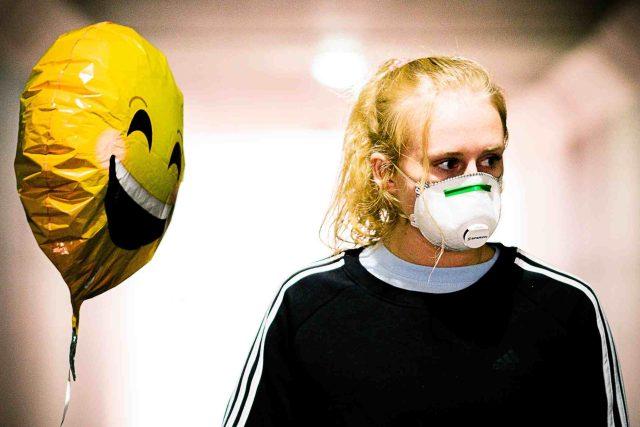 Žena s respirátorem a balónkem