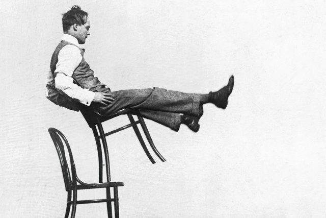 Muž balancující na židlích značky Thonet