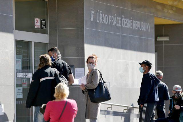 Fronta lidí v rouškách a bezpečnostních rozestupech před úřadem práce